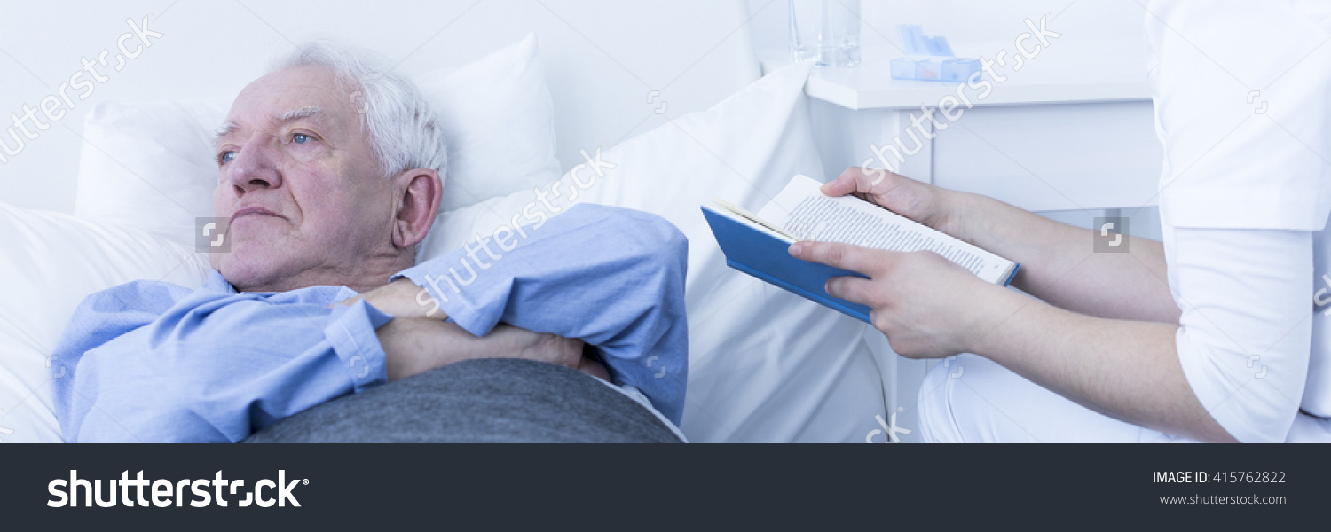 stock-photo-hospice-pensioner-lying-in-bed-caregiver-reading-book-sitting-next-to-patient-s-bed-in-light-415762822