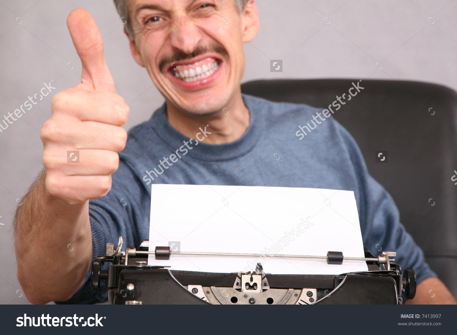stock-photo-man-after-the-typewriter-shows-gesture-by-the-finger-7413997