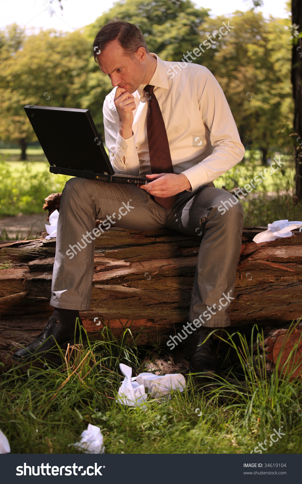 stock-photo-businessman-working-on-laptop-in-a-city-park-34619104