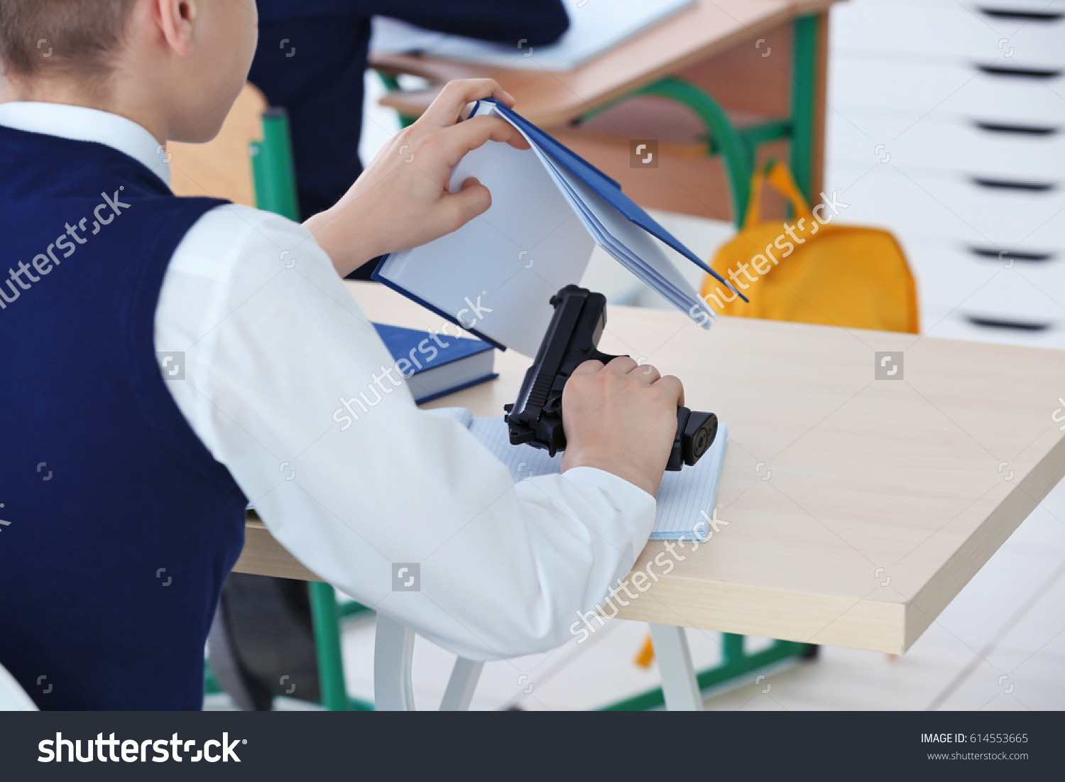 stock-photo-closeup-of-schoolboy-sitting-at-desk-in-classroom-and-holding-gun-614553665