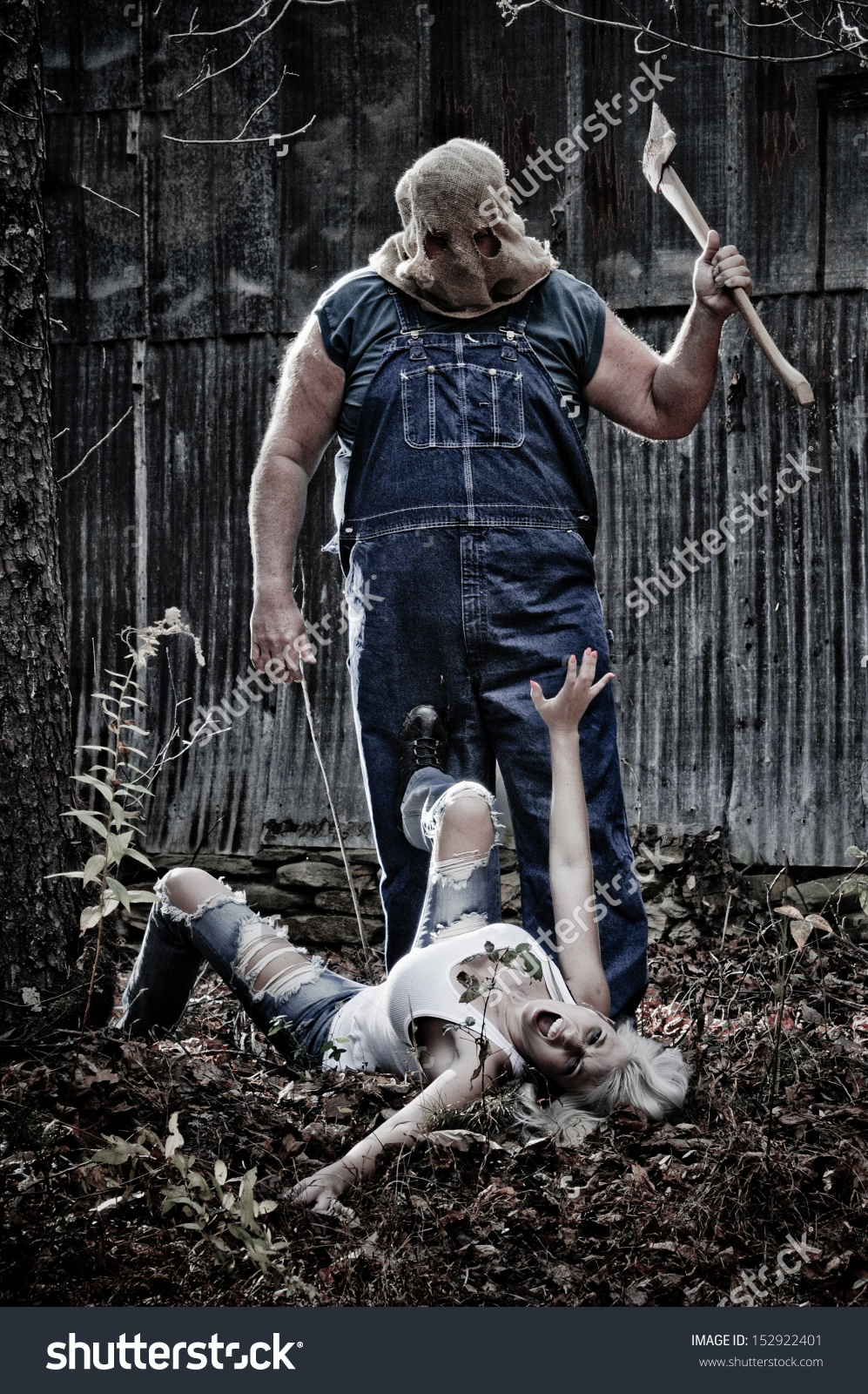stock-photo-horror-scene-of-a-woman-crawling-in-the-woods-away-from-a-hooded-man-with-an-axe-152922401