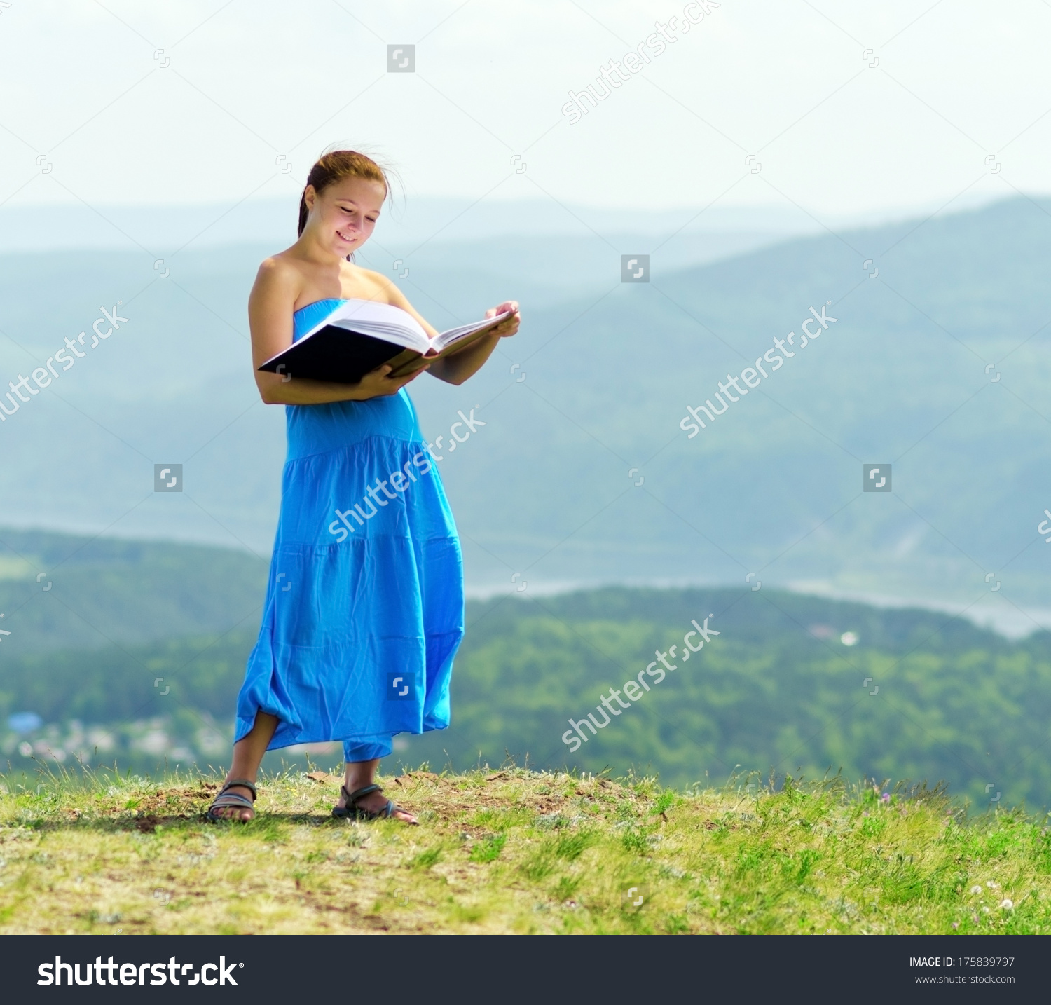 stock-photo-red-haired-woman-with-book-on-the-hilltop-175839797