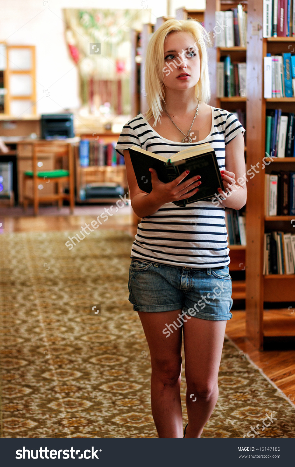 stock-photo-schoolgirl-in-the-library-teaches-verse-by-heart-holding-an-open-book-in-his-hands-on-the-415147186