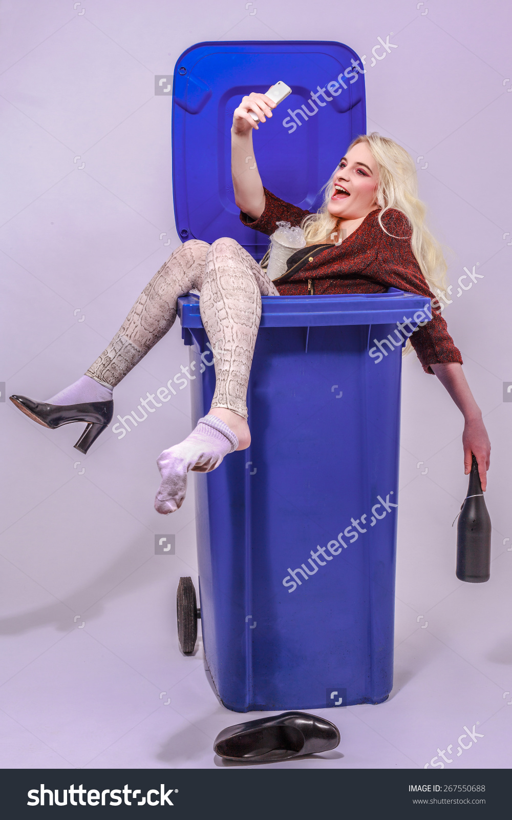 stock-photo-young-alcohol-impaired-girl-with-long-blond-hair-sitting-laughing-in-a-blue-garbage-can-and-makes-267550688